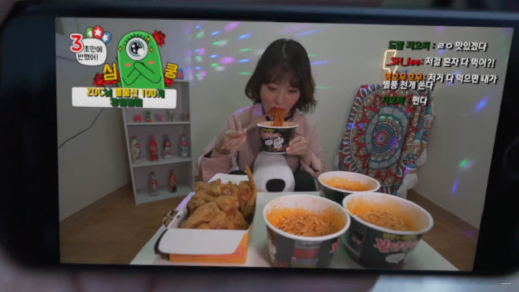 疏離的人際關係,寂寞的一邊吃著晚餐,一邊看著手機裡女性大胃王的Youtuber影片
